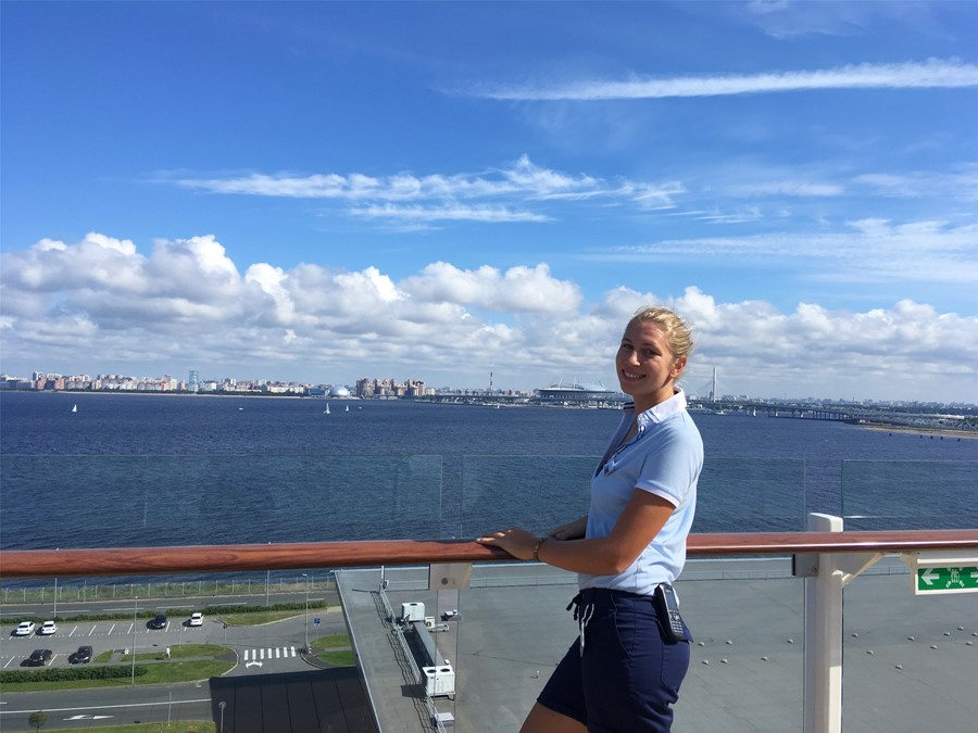 <p>Toril Heming in Uniform auf Deck 14. Im Hintergund die Skyline von St. Petersburg.</p>